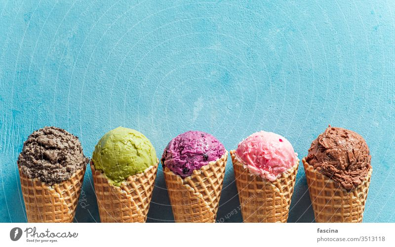 ice cream scoops in cones with copy space on blue gelato sundae banner background summer above ball biscuits blueberry chocolate cold colorful concept cookies