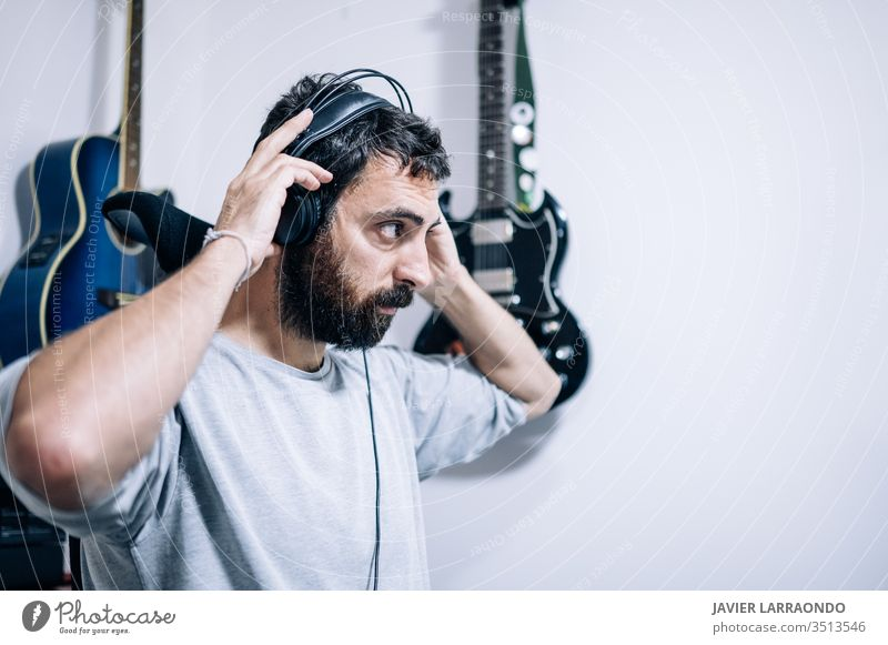 Working sound engineer wearing headphone in home studio. man composer learning guitars headphones artist audio back backgrounds digital entertainment computer
