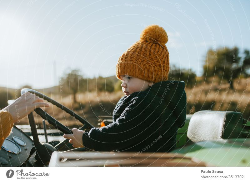 Child on the steering wheel childhood Steering wheel Driving Transport Colour photo Human being outdoors Exterior shot 1 - 3 years Childhood memory Infancy