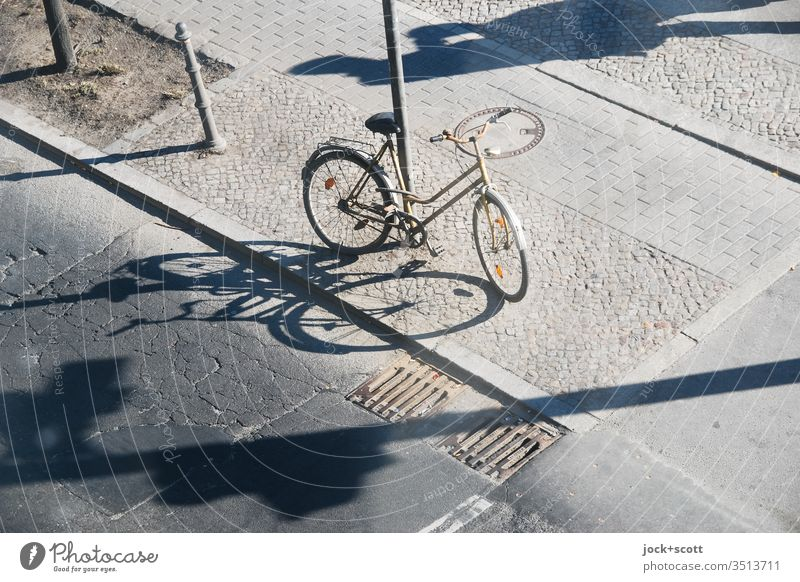 with long shadows centrally located Bicycle Asphalt Street Traffic infrastructure Associated stake Sidewalk Cobblestones cracks Curbside Abstract Gully