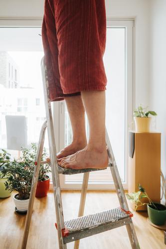 caucasian man barefoot on ladder adult caucasian ethnicity danger dangerous day domestic domestic life feet fixing home home improvement home repair homeowner