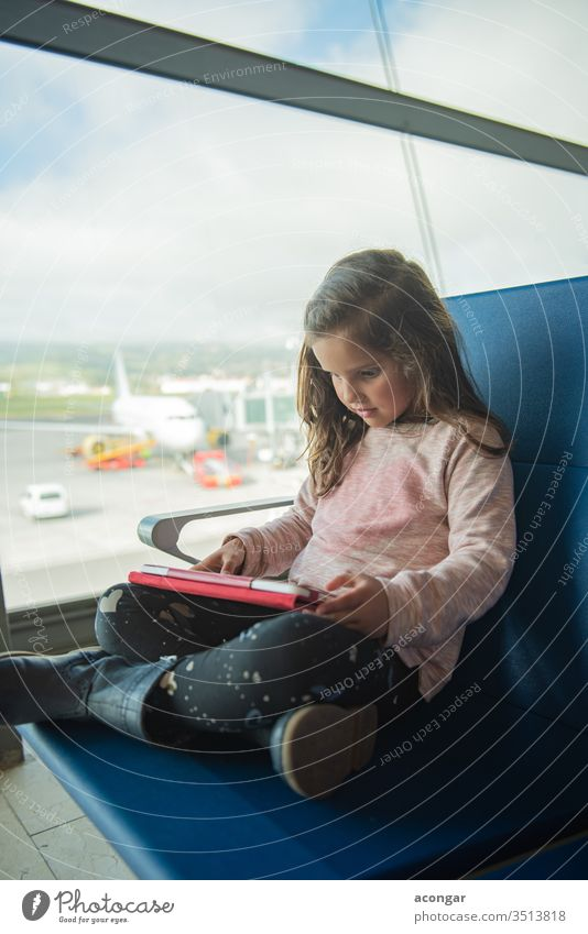 Little cute girl waiting for plane at airport terminal, using digital tablet Child adorable aircraft airline caucasian chair childhood computer delay departure