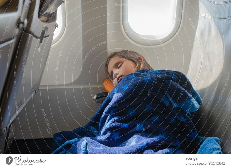 Girl sleeping inside the airplane during the flight Child aeroplane aircraft airline bedtime blanket boring caucasian chair childhood comfortable cover cute