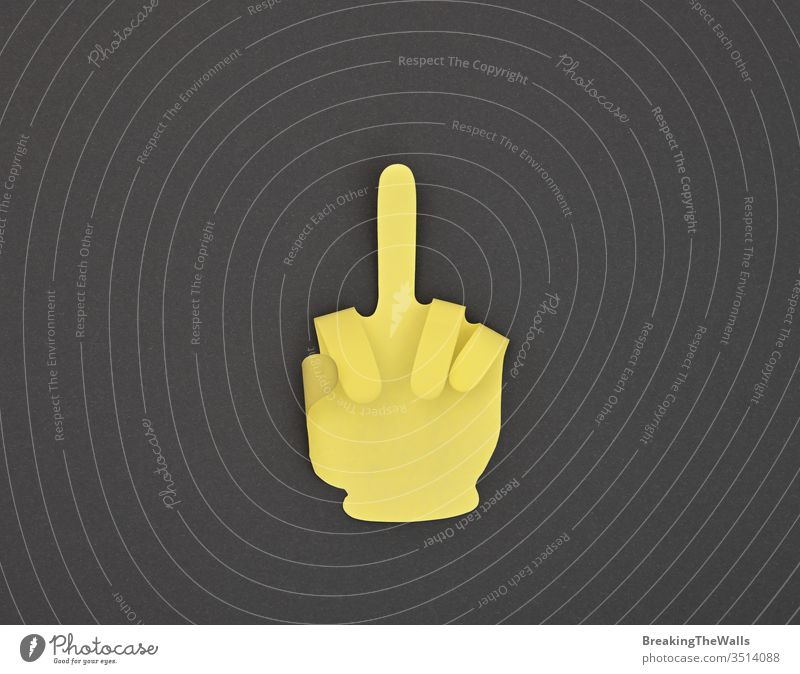 Paper made finger rude gesture sticker on grey one middle insult offensive hand shape paper yellow closeup note black background dark business metaphor concept
