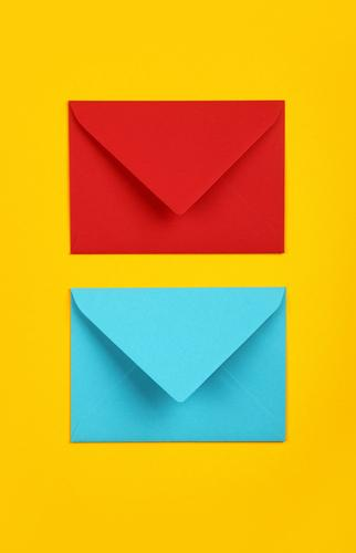 Two closed blue and red paper envelopes on yellow Envelope two pastel vivid background closeup color colorful multicolor post mail message communication blank