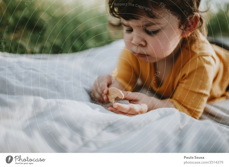 Little girl eating cookie lying on the grass Child Portrait photograph Cookie Eating Joy Grass Nature Natural Lifestyle Caucasian Happy Infancy Happiness Love