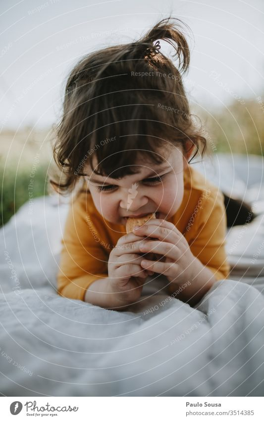Child eating cookie lying on grass Grass Green Joy Meadow Garden Nature Summer Infancy Cute Beautiful Exterior shot Happy Delightful Happiness people Spring