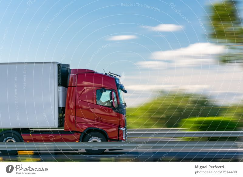 Truck with refrigerated semi-trailer driving on the highway with a blue sky with some clouds truck controlled temperature cargo moving perishable shipping road