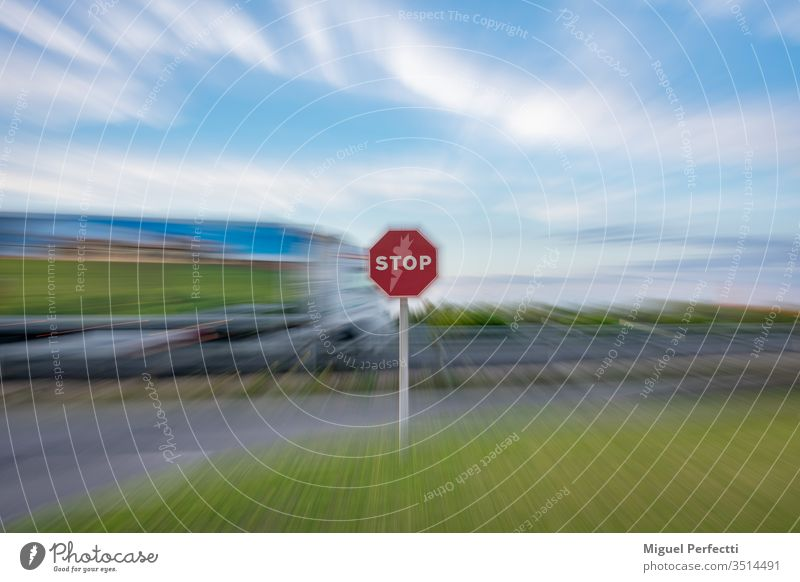 """""""Stop"""" traffic sign and a moving truck driving on the road, all under a zoom effect stop stop sign symbol warning danger safety red blue sky white halt"""