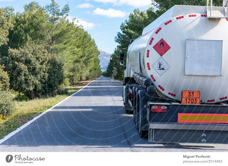 Hazard labels for flammable and polluting liquid on a fuel tank truck driving on a narrow, straight road lined with trees. road transport dangerous liquids