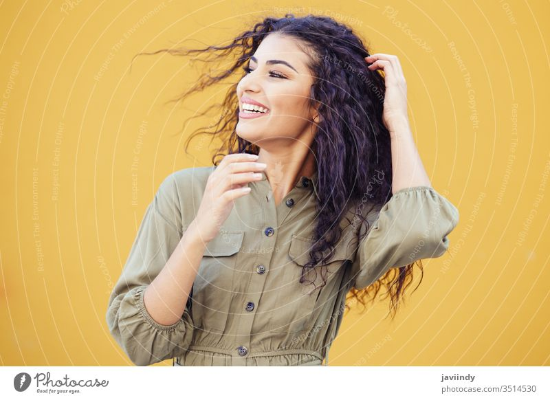 Arab woman with curly hair moved by the wind arab hairstyle smile beautiful girl beauty young one fashion female arabic copyspace middle eastern yellow green