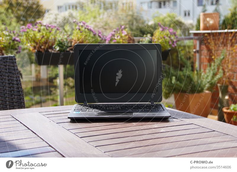 Laptop on terrace table in front of flowers laptop Notebook Computer outdoor Balcony Terrace Window box home office spring labour