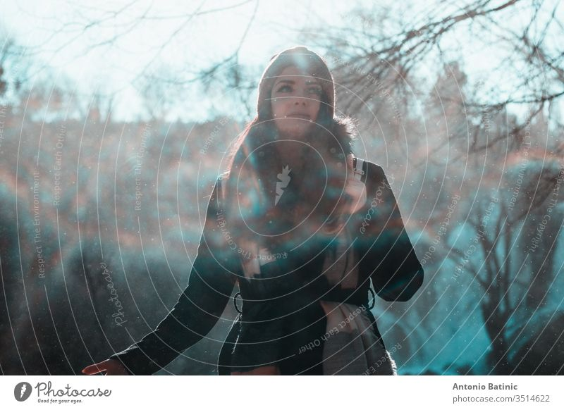 Attractive brunette in winter clothing and an orange head scarf posing on a cold winter day looking into the distance. Water droplets flying everywhere creating a mist,fog and mini rainbows