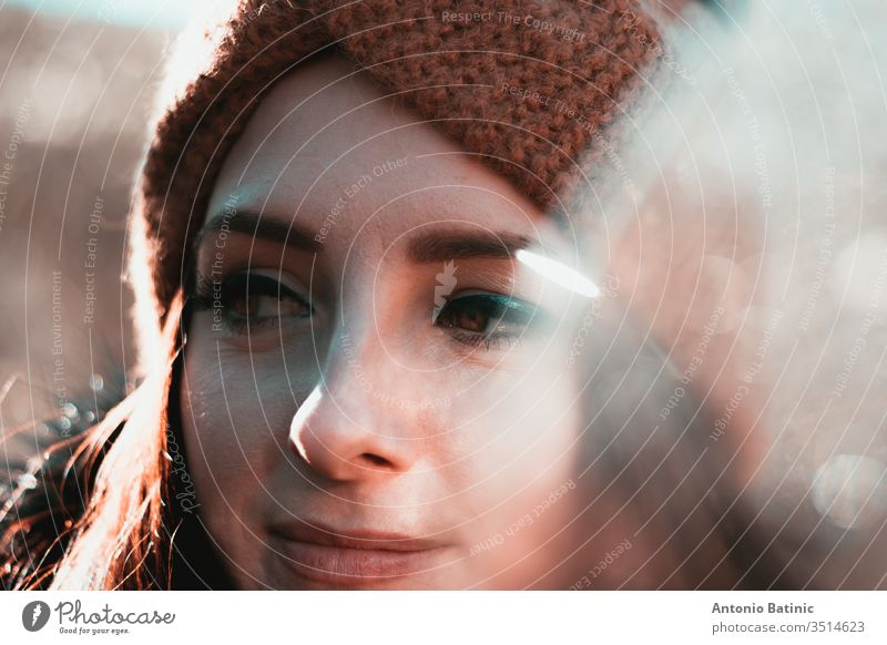 Closeup headshot of an attractive brunette in winter clothing and an orange headband. Cold winter day in the forest, serious happy face looking into the distance thinking