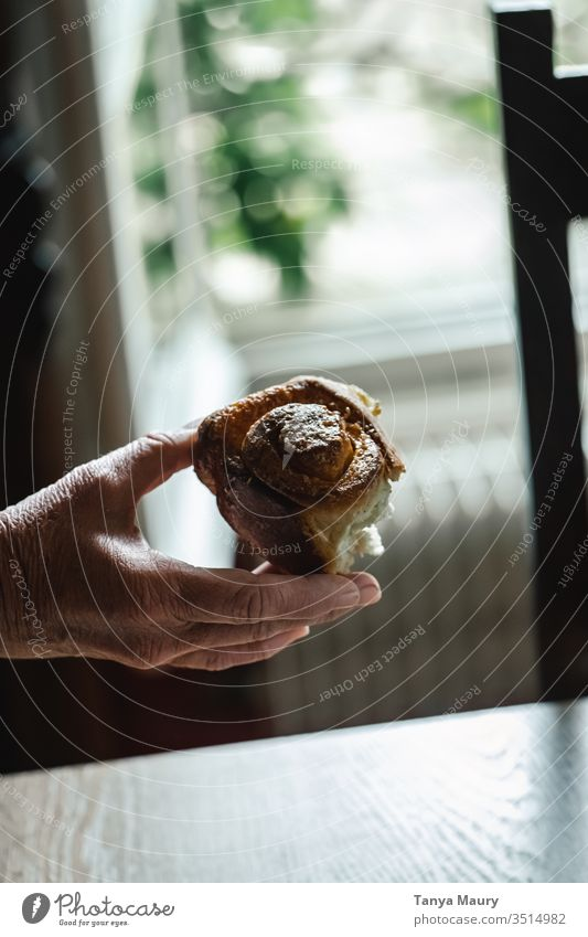 Hand of a woman holding a cinnamon roll hand cinnamon rolls cinnamon cake cinnamon bun Cinnamon eating piece of cake bread Food photograph people natural light