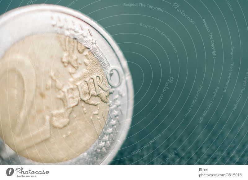 Close-up of a two euro coin against a turquoise background; money, finances Money Macro (Extreme close-up) Euro Bright Financial Statements Save