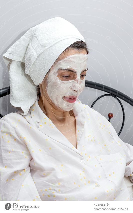 Mature woman taking care of her face with a face mask in bed with dog beauty treatment facial mature laptop covid-19 coronavirus quarantine epidemic job work