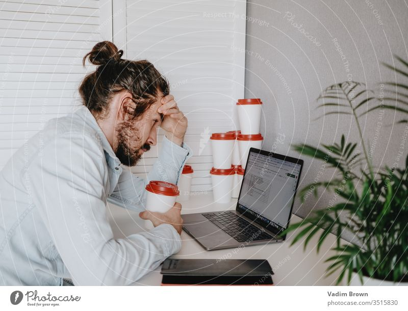 Exhausted young man with beard sitting on the chair and using laptop. video chat online shopping using technology work from home millennial business phone