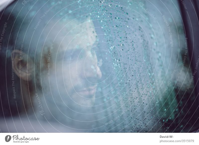 Man looks out of the car through the wet window in the rain Looking Motoring Rainy weather Autumn Bad weather Dreary tribulation depressive Street Gray Weather