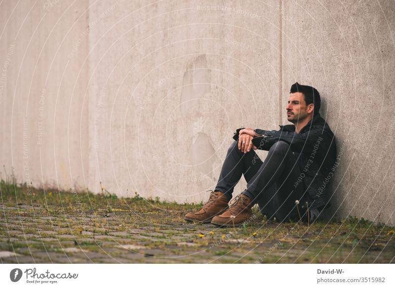 Man sits lonely on a wall Lonely Wall (building) out by oneself Meditative frustrated Frustration Copy Space top Copy Space left Copy Space middle Model