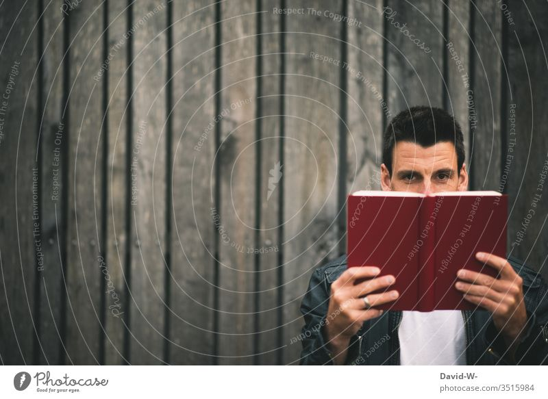 Man holds a book in his hands in front of a wooden wall and looks into the camera Book Wooden wall Reading Education educated Study Reading matter Page Reader