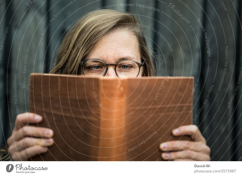 Woman with glasses holds a book in her hands and reads Book Reading youthful Reader hollowed Eyeglasses Nerdy naturally Tension Literature Education