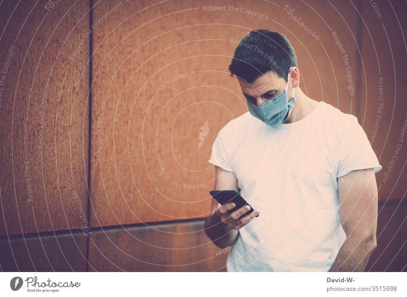 Corona - Man with mobile phone in his hand Respirator mask coronavirus Virus Reading Manipulation message transmission Self-made Mask Write Illness Healthy