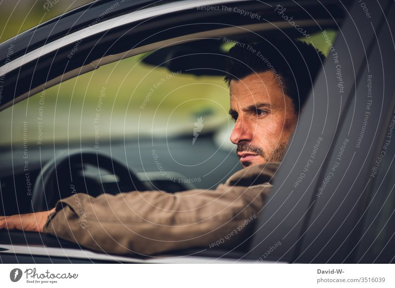Man sits in car and looks seriously out the window Earnest view outside Rear view mirror Mirror look back Road traffic Car Window Open Exasperated Sour Evil