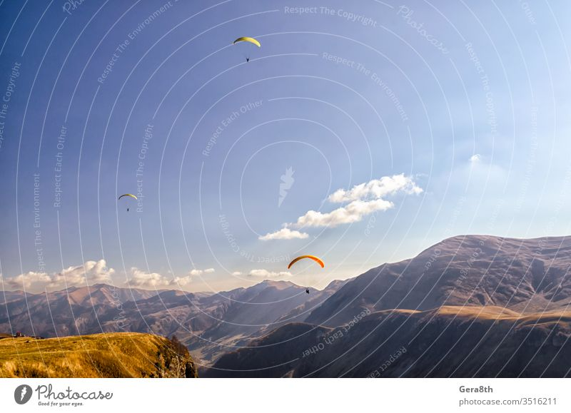 three paragliders in sky against the background of Caucasus mountains adrenalin clouds day europe extremal extreme extreme sport fly flying grass high