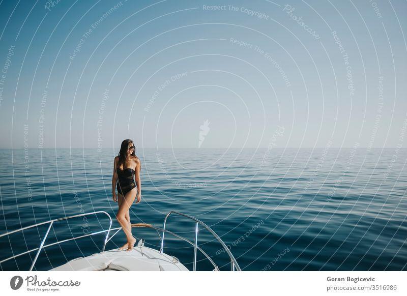 Young woman in swimwear standing on yacht front adult attractive beautiful beauty bikini blue boat boating body brunette caucasian cruise day deck enjoying