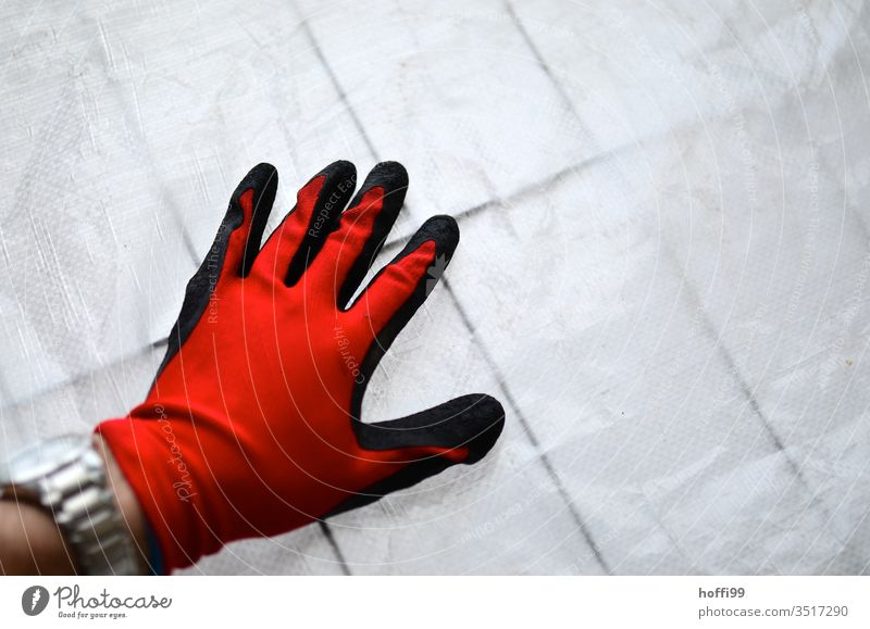 Red glove on construction tarpaulin on the barrier grid Gloves Workwear Protective clothing Work gloves Work and employment Profession Construction site