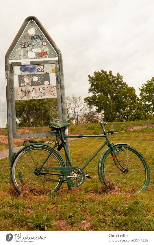 green bicycle connected to a sign Bicycle Associated Road sign Meadow turned off Lonely Exterior shot Transport Colour photo Deserted Signage Safety