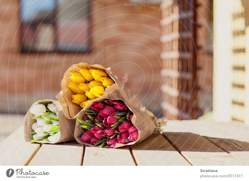 Beautiful colorful bouquets of tulips in craft paper lie on the street on a wooden table. Side view market flower spring red pink march decoration floral green