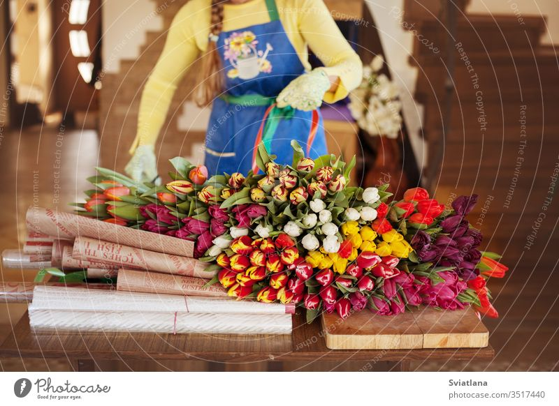 Girl florist is packing beautiful tulips in a flower shop in kraft paper. Women's Day and Valentine's Day bouquet hands view pink packaging girl woman