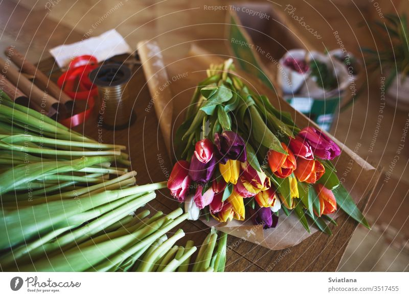 A huge multi-colored bouquet of tulips lies on a table in a flower shop. Preparing for Women's Day and Valentine's Day hands paper view pink packaging girl