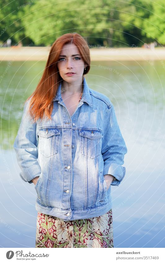 authentic young woman wearing denim jacket over summer dress standing by lake girl jeans adult person people women red hair redhead caucasian pretty female