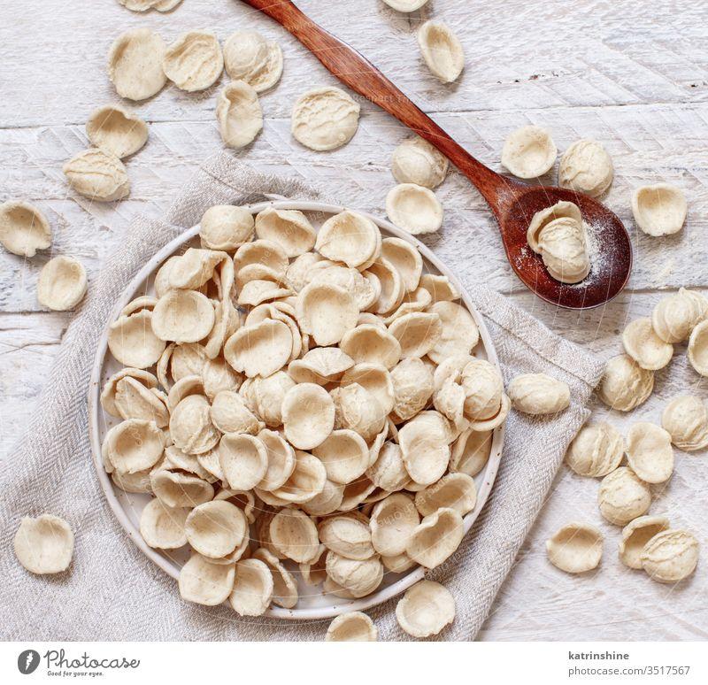 Fresh raw  italian pasta orecchiette apulia fresh dry traditional ingredient top view knife dark plate diet flour handmade homemade mediterranean organic