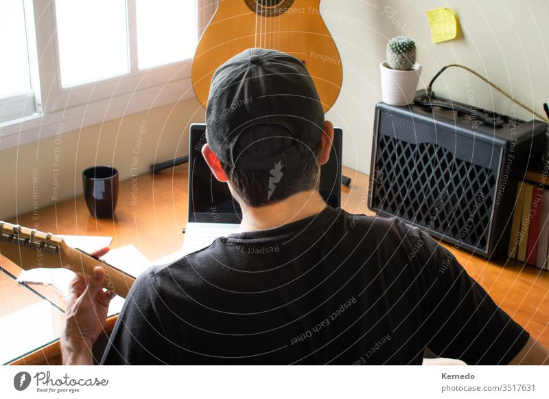 Young musician in cap learning to play the guitar using a computer at home. Concept of learning music with online classes, using technology. laptop practice man
