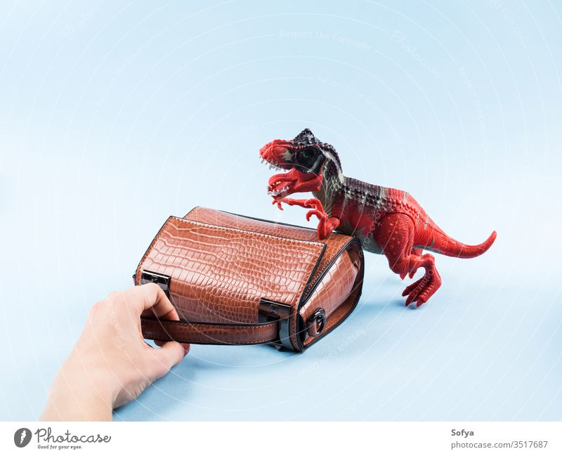 Angry dinosaur toy and lady hand bag fashion woman shopping sale reptile accessory handbag shoulder bag small desire store angry madness abstract print teeth