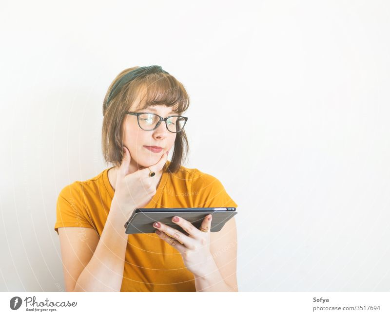 Smiling young woman in yellow using tablet. online shopping person mobile student lifestyle quarantine school adult smiling stay home smart cute funny portrait