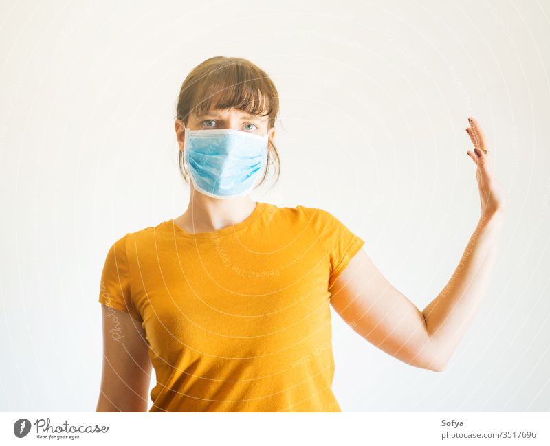 Young woman in face mask with raised arm coronavirus social distancing quarantine hand stop isolated covid19 distant stay home alone protection isolation
