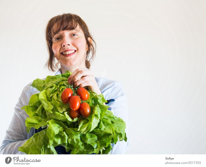 Woman in blue apron with fresh produce in hand food delivery grocery store shop owner local groceries hands green staples safe girl foodstuff face holding