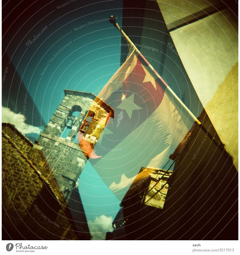 Double exposure of a street in Italy with a tower and a flag - analog Analog Holga Slide Lomography Scan Experimental Cross processing cross Sky