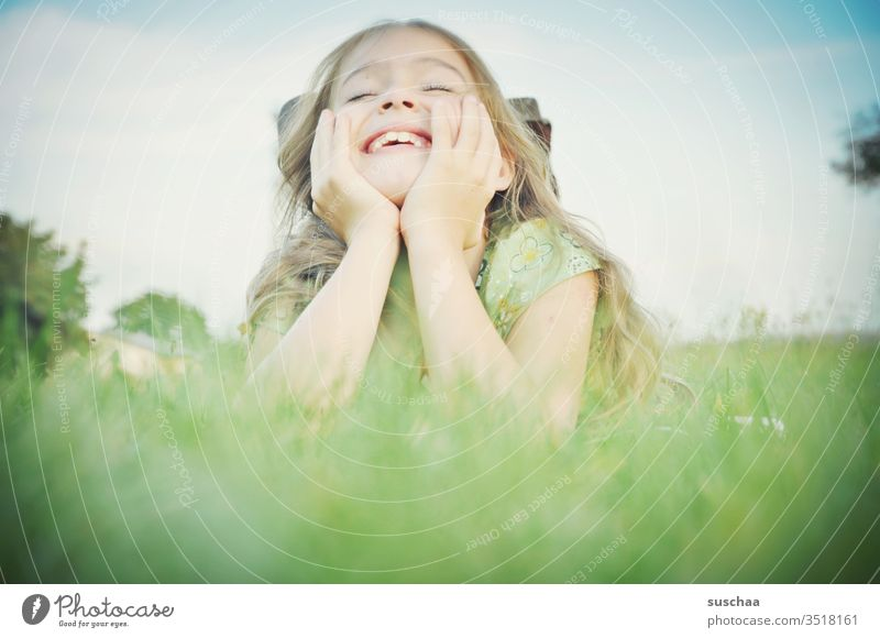 girl lies on propped up arms in the grass and laughs Child Infancy Joy Laughter Joie de vivre (Vitality) fun Ease Face hands Grass Lie smile luck Happiness
