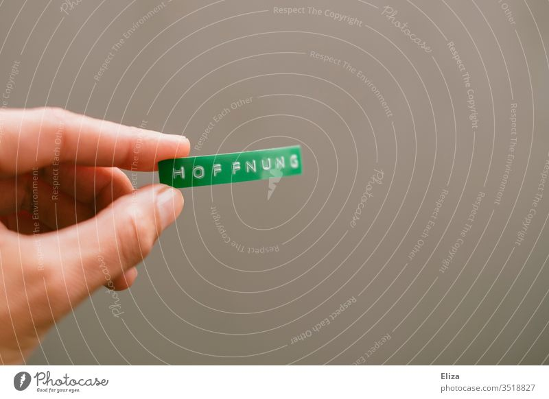 A person holds a green sign with hope written on it in his hand Hope Climate nature conservation by hand stop Word Text Letters (alphabet) writing Label