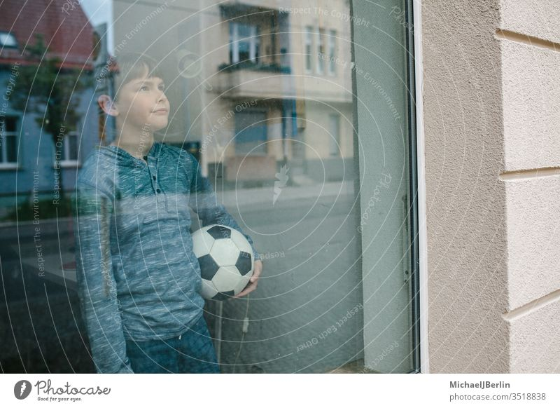 Boy stands at the window with a football and looks sadly outside, symbolizing the isolation of children during Corona Pandemic Child Boy (child) soccer inside