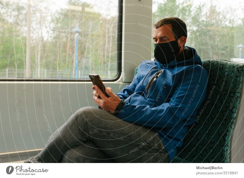 Man with fabric mask or mouth-nose protection in public transport during coronavirus pandemic outbreak Face mask Mask Mouth and nose mask Commuter trains Track