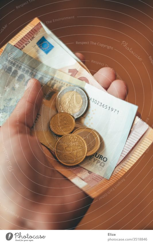A person holding euro banknotes and coins Money Euro Notes by hand stop Give finance gratuity Paying Coin Financial Industry Loose change pay cash Shopping