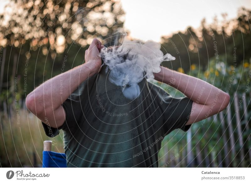 The young man in the garden pulls his T-shirt over his smoking head on a summer evening Smoke Smoking Man Tobacco Addiction Nicotine Tobacco products Dependence