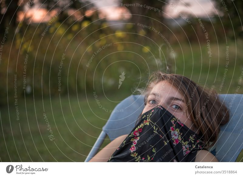 Evening mood in the garden, the brunette young woman in a deck chair has pulled her T-shirt over her mouth and nose and looks into the camera Young woman